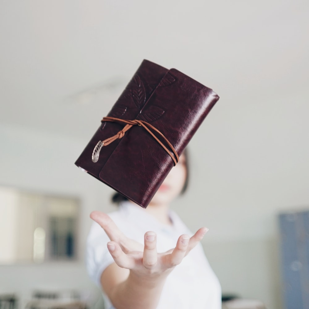 brown leather clutch wallet in mid air above woman's hand