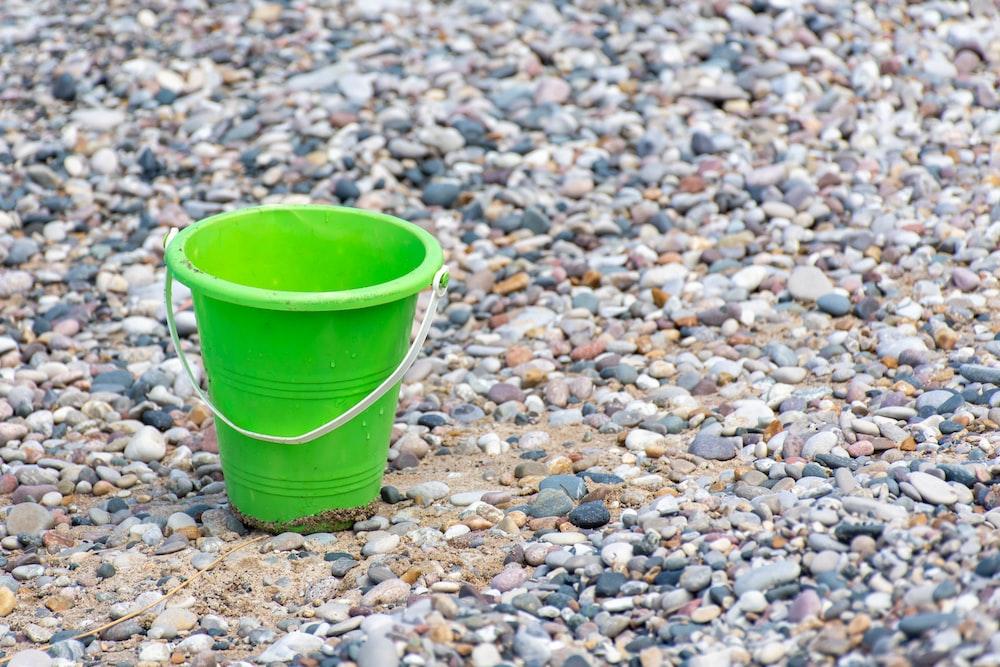 green plastic bucket on stones