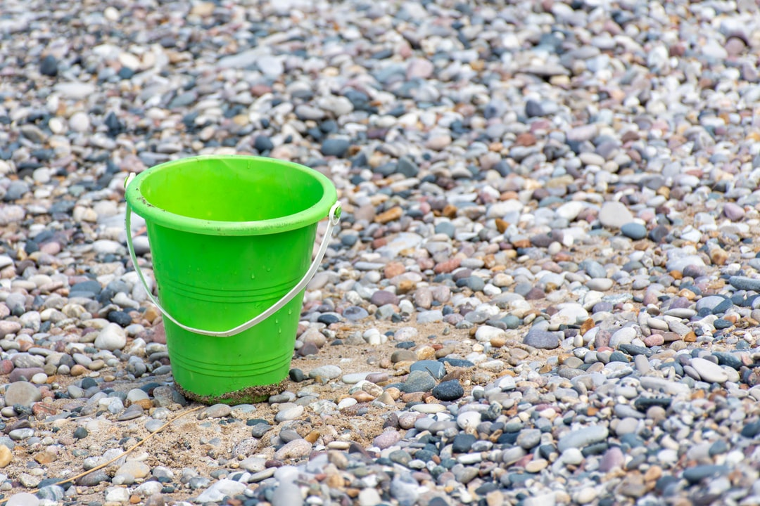 Close up of Green bucket or pail on the seashore sitting empty in the rocky sand next to the lake with blue water in background and open concept space.  background, beach, beautiful, blue, bright, bucket, child, coast, color, colorful, colour, empty, fun, green, ground, holiday, lake, leisure, lying, ocean, outdoor, outside, pail, plastic, play, rocks, sand, sandy, scoop, sea, shore, shovel, side, spade, summer, sunny, top, toy, toys, travel, vacation, view, water