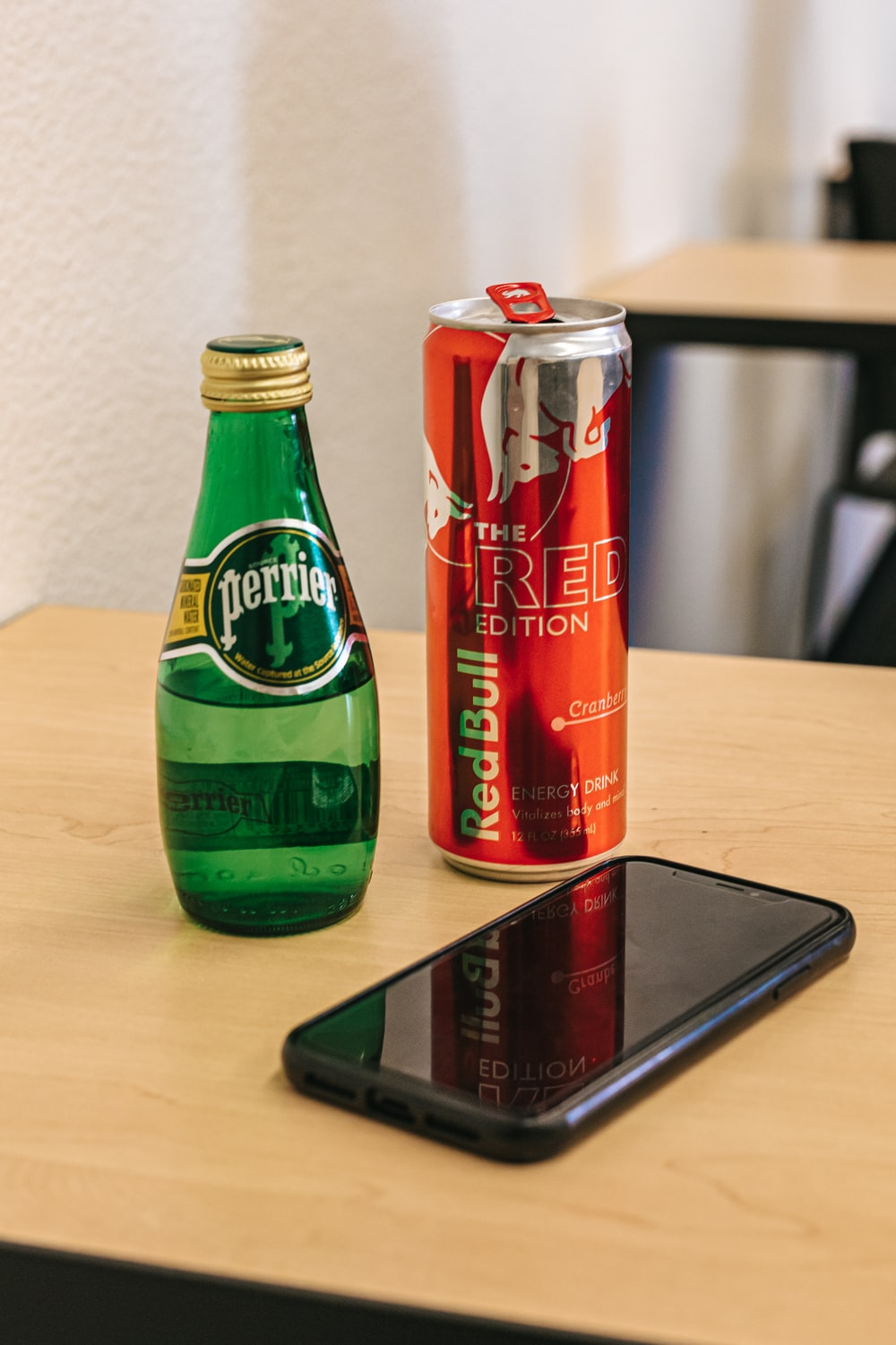 two soda cans beside smartphone