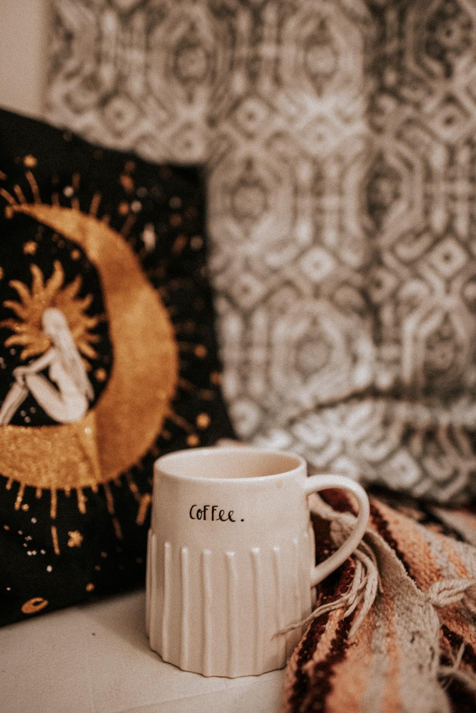 white mug beside gray textile