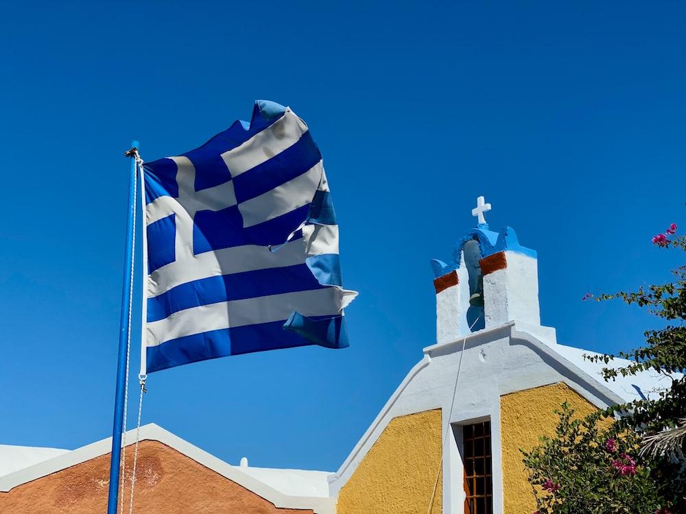 white and blue flag near church
