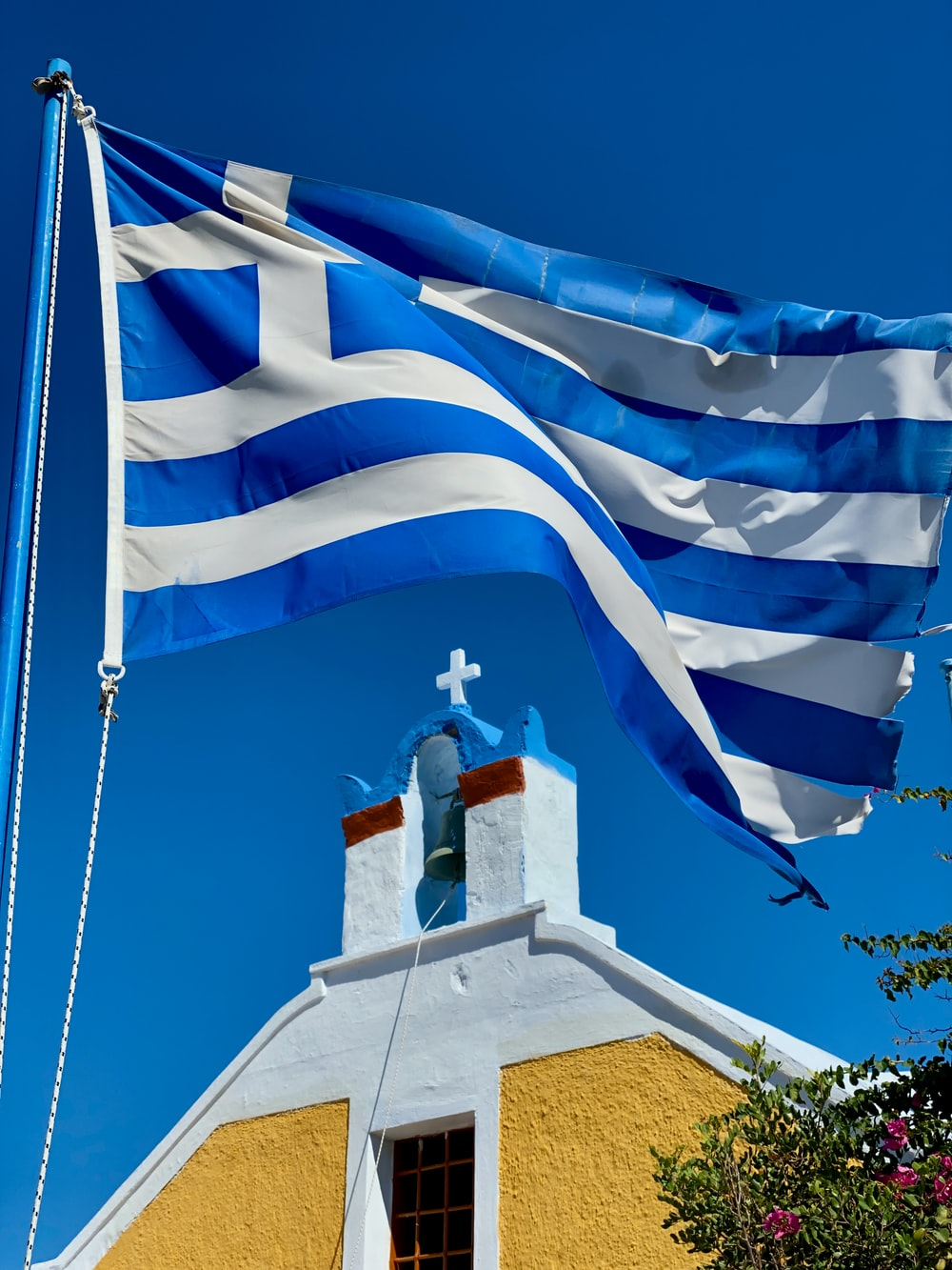 raised Greece flag near cathedral during daytime