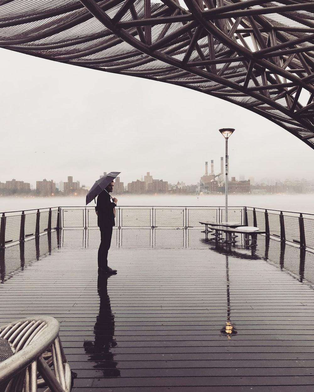 man standing on the ocean dock holding umbrella