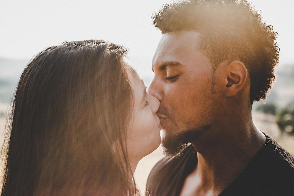man kissing woman during daytime