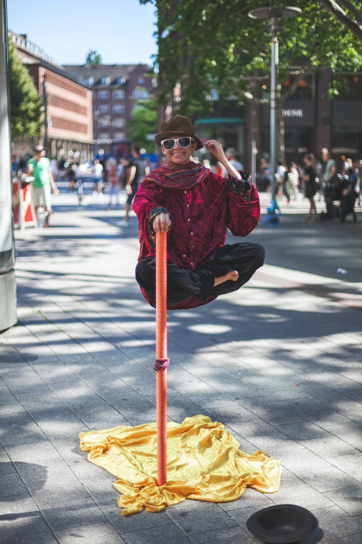 man floating holding on orange stick white people watching on the street