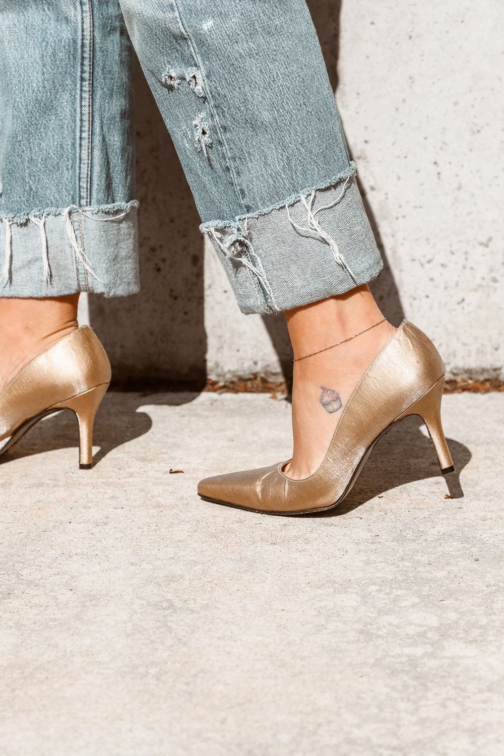woman in gold heeled shoe with blue denim jeans