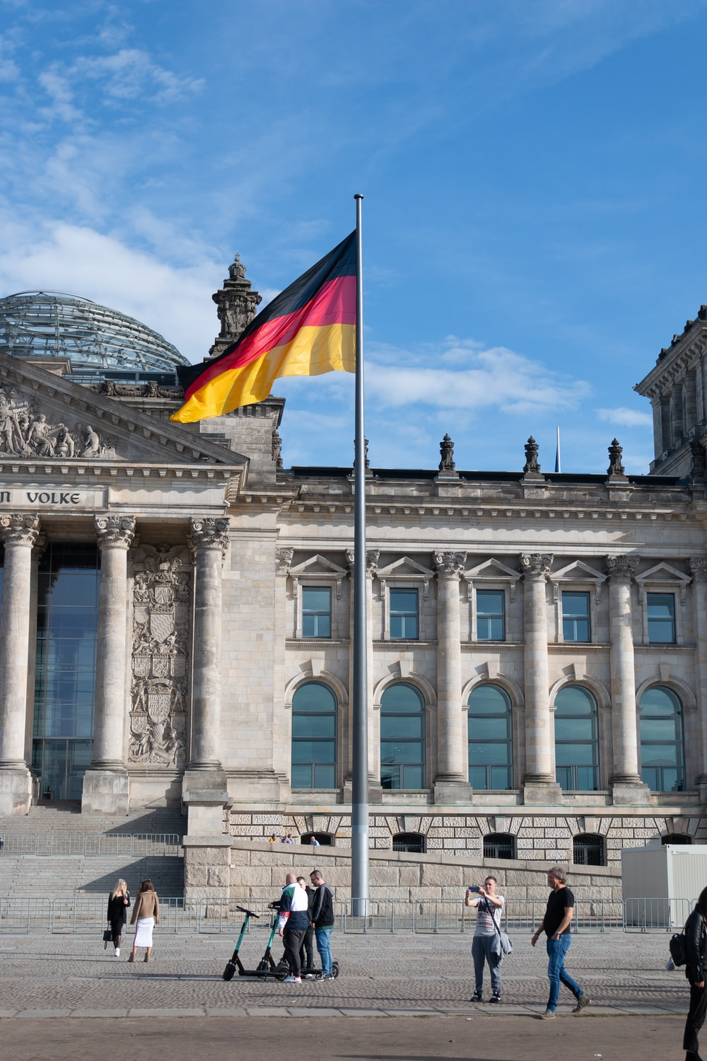 people walking beside building with waving flag of Germany on pole