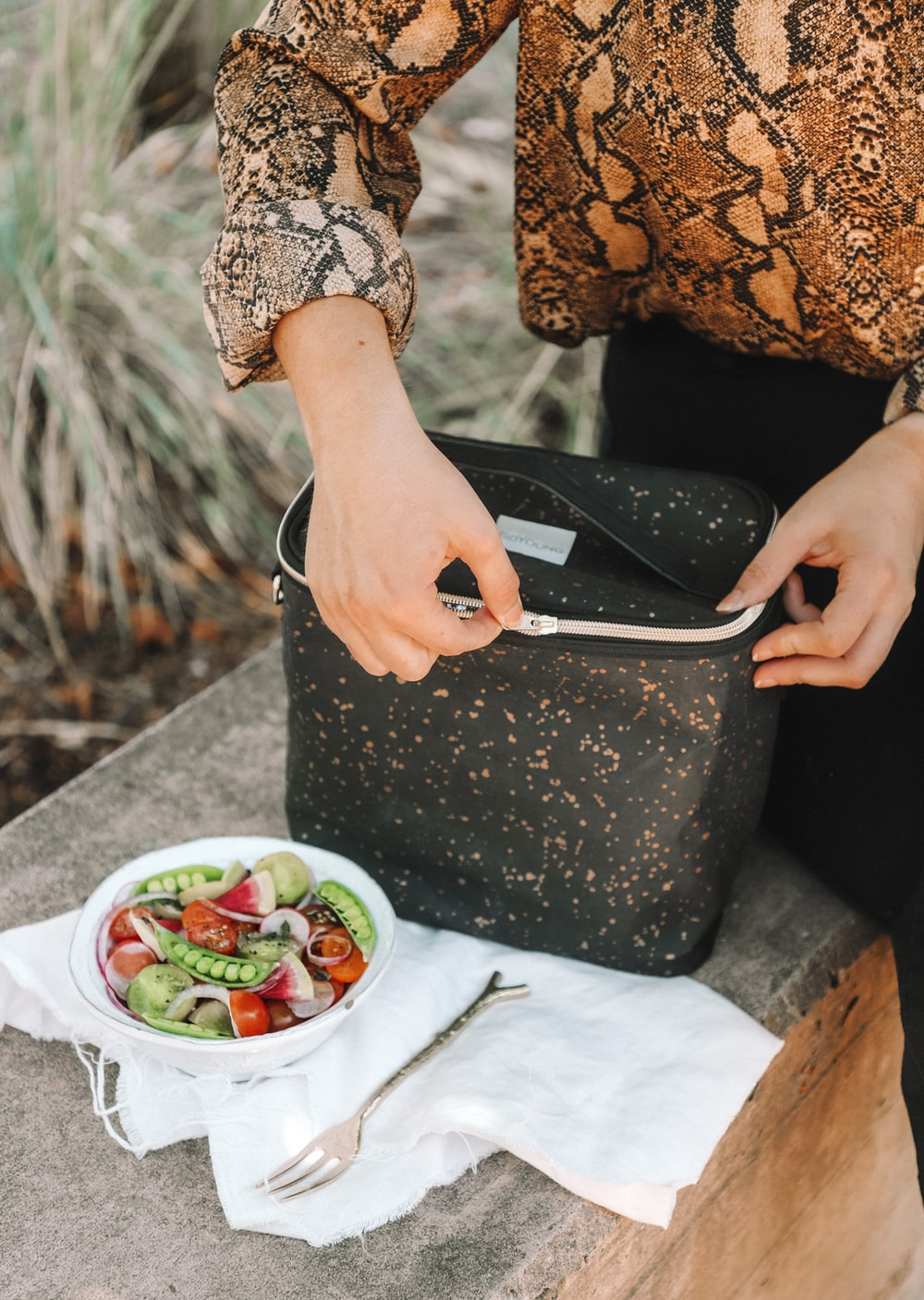 woman opening lunch bag near bowl of salad