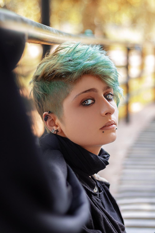 woman wearing black top leaning on metal railings