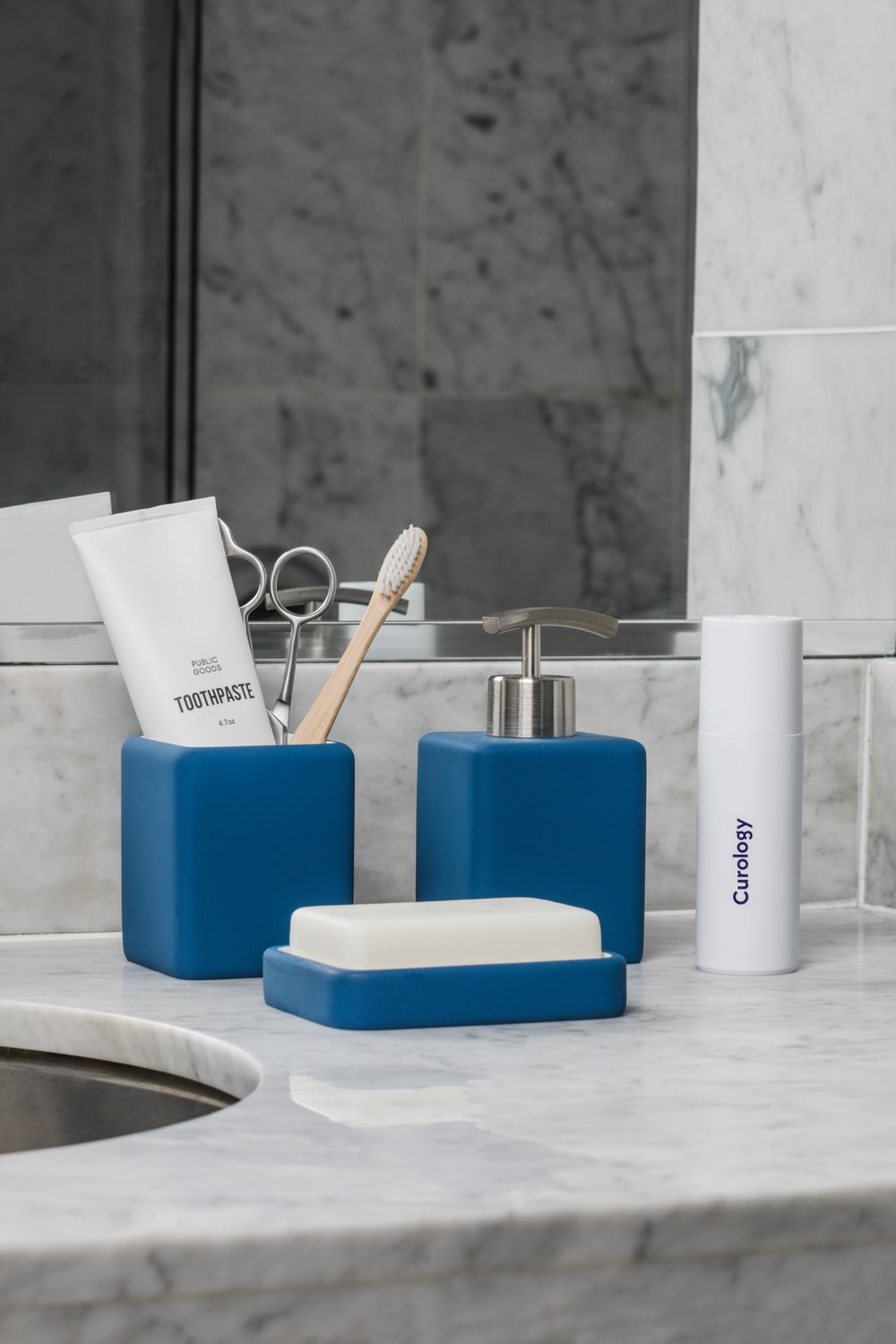 white soft-tube and brown brush in blue container beside pump bottle