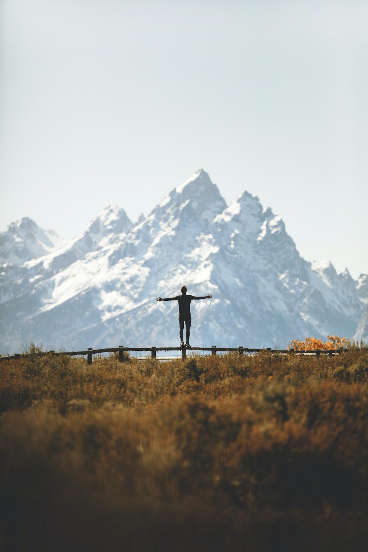 man standing on fence overlooking mountain range