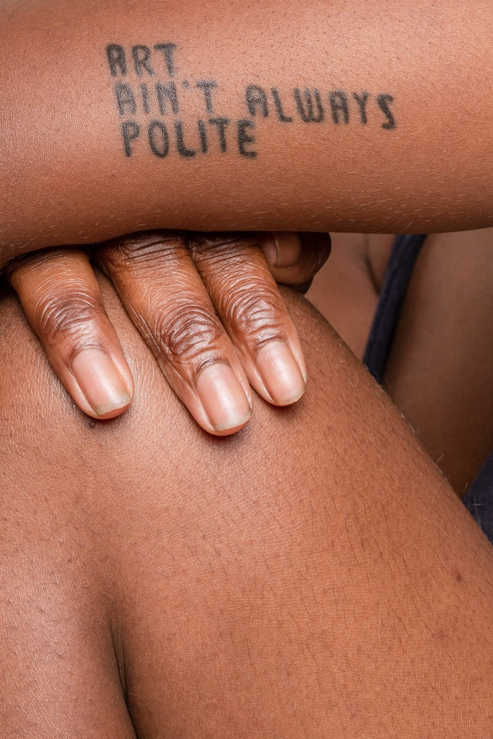 person showing Art Ain't Always Polite tattoo