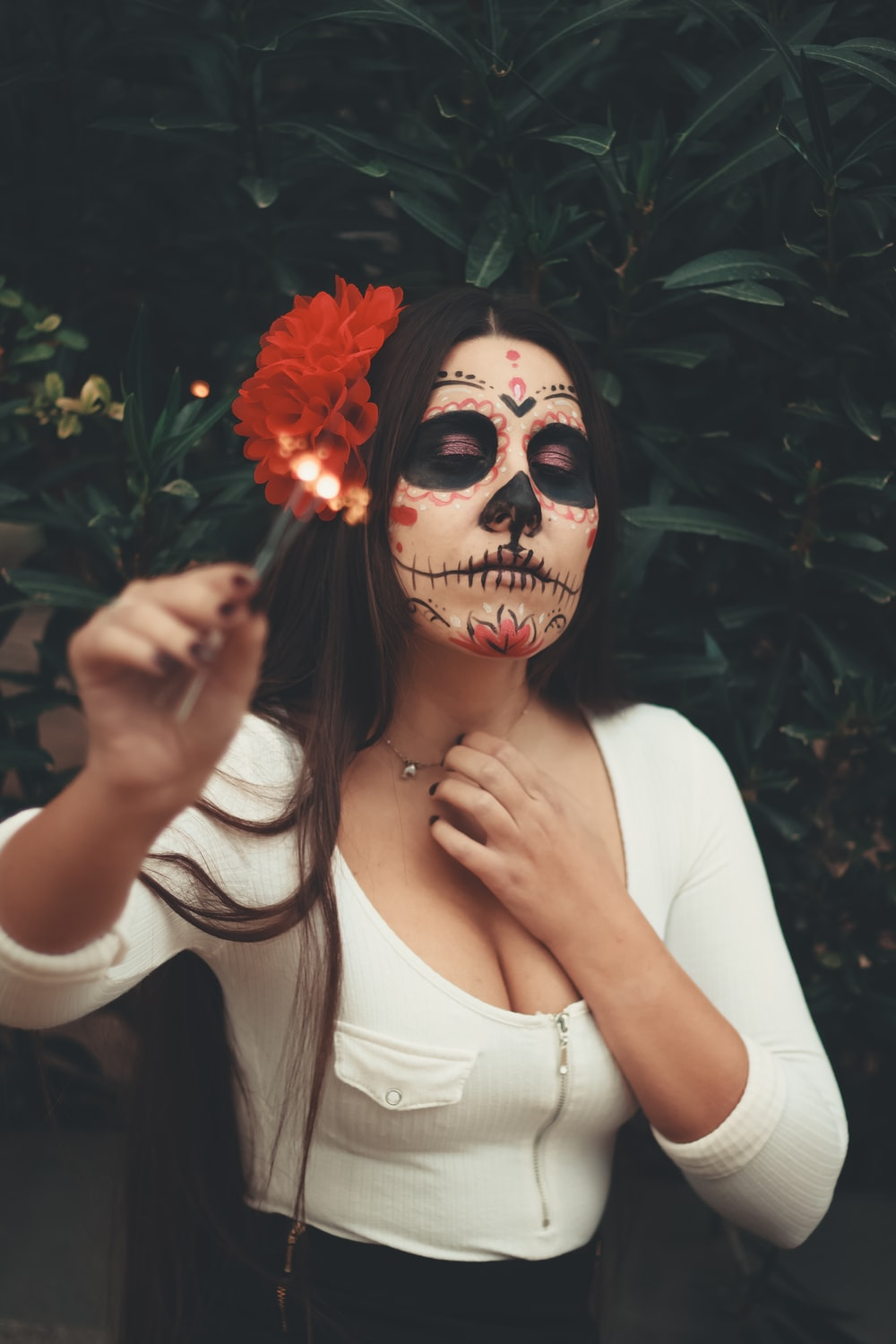 woman holding flower with face paint