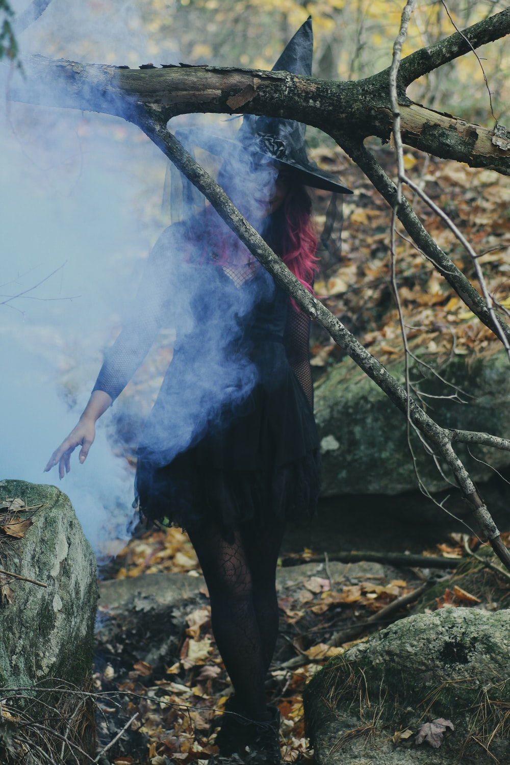 woman in witch costume standing beside rock
