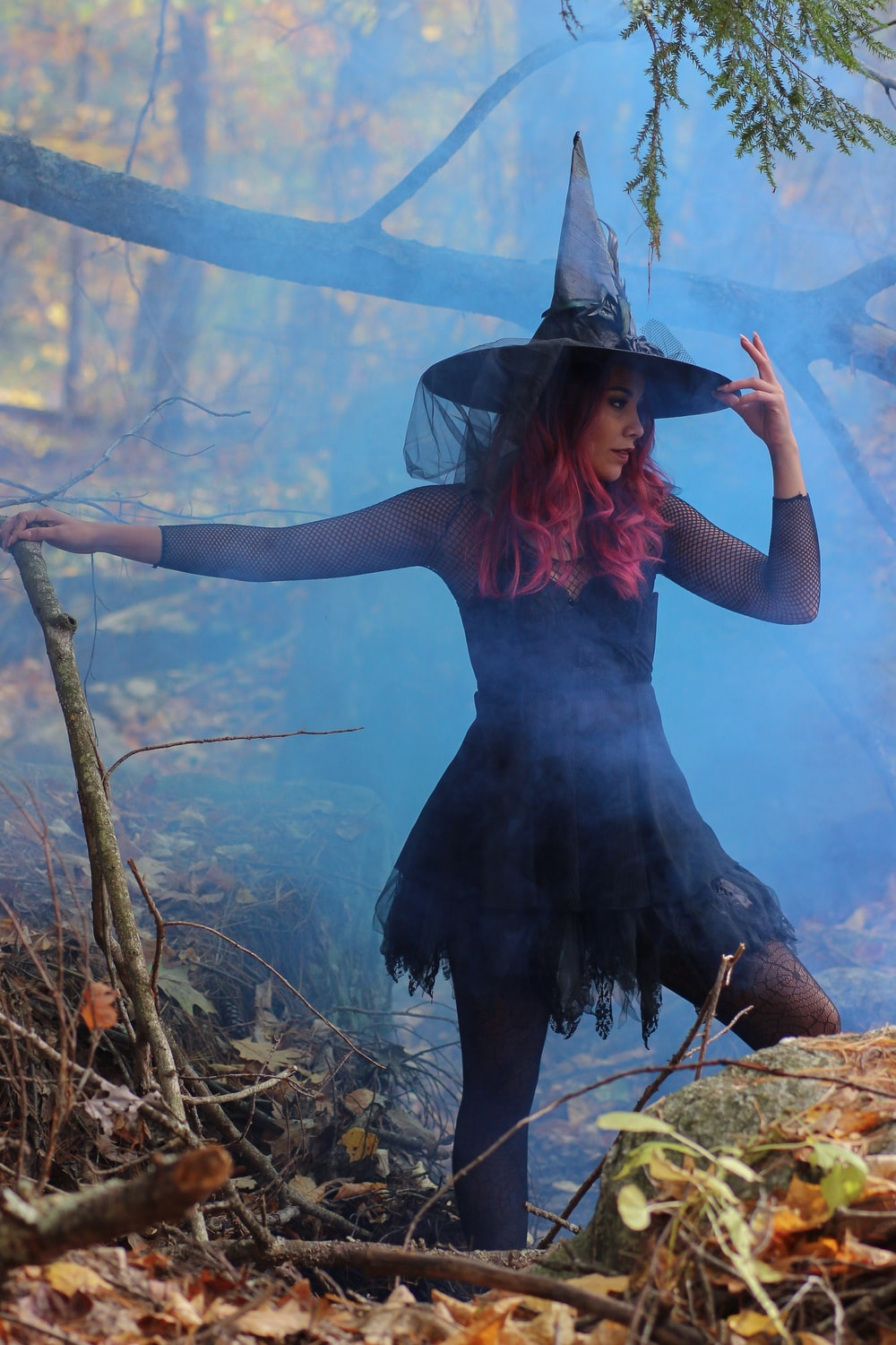 woman in black witch costume standing beside rock