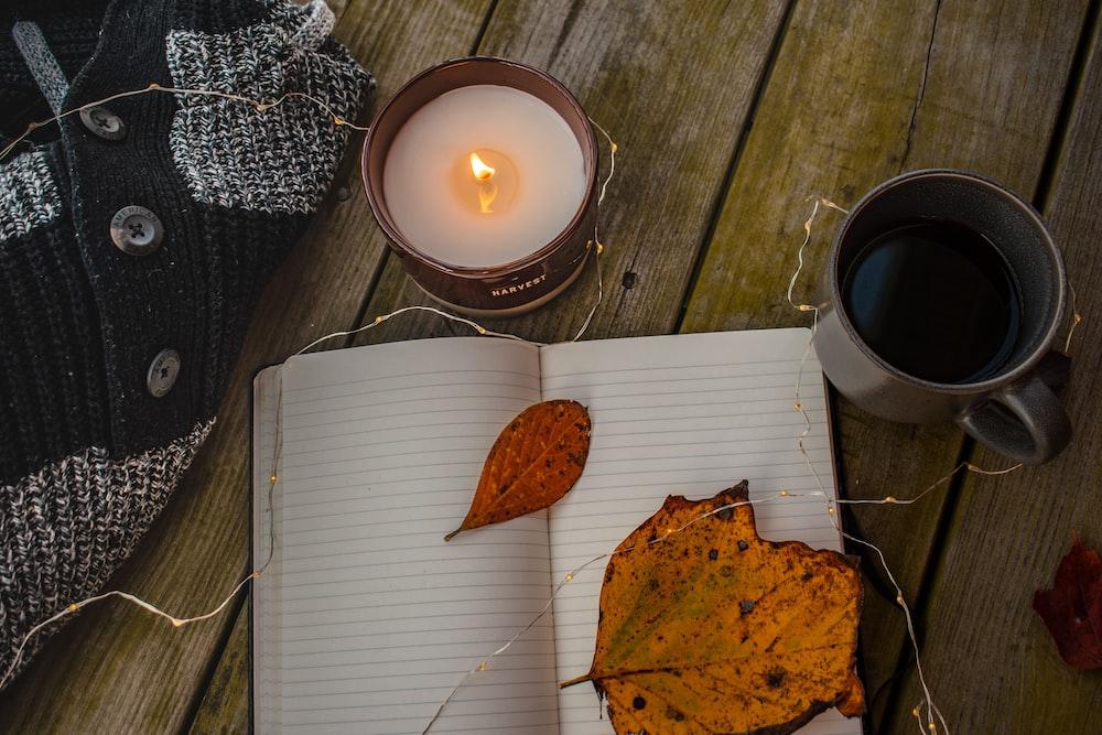 notebook beside mug and candle