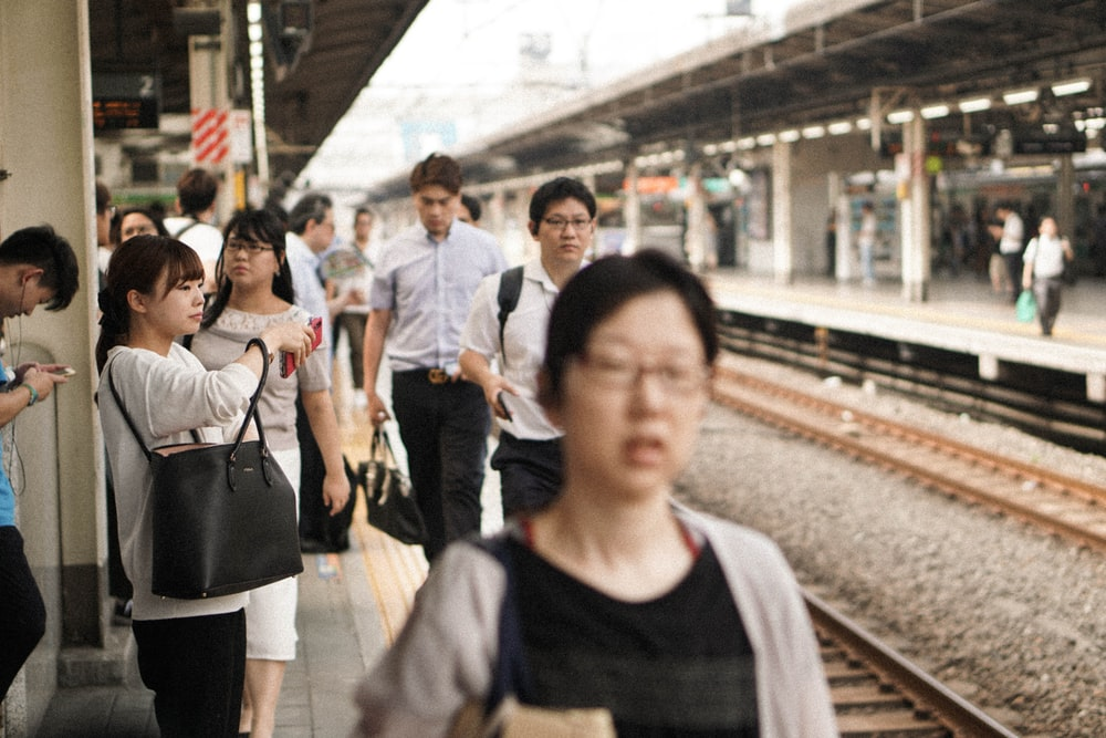 photo of man wearing white dress shirt and black pants walking on train station