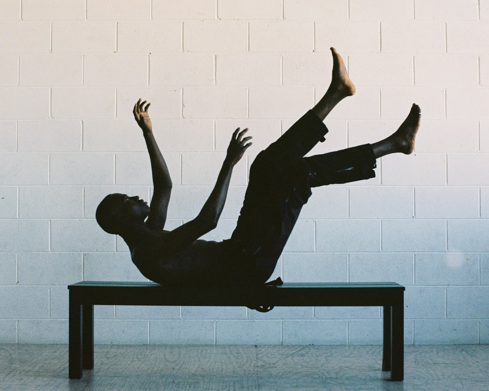 man lying on black wooden table