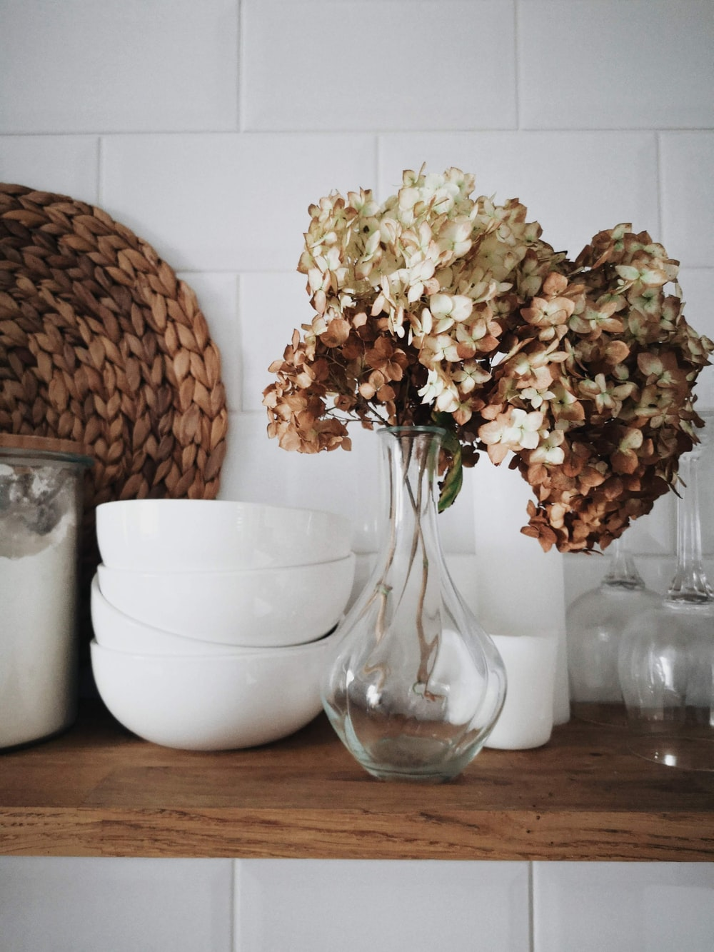 flowers in vase beside dishes