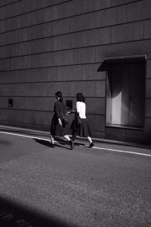 two women walk on the street in monochrome photo