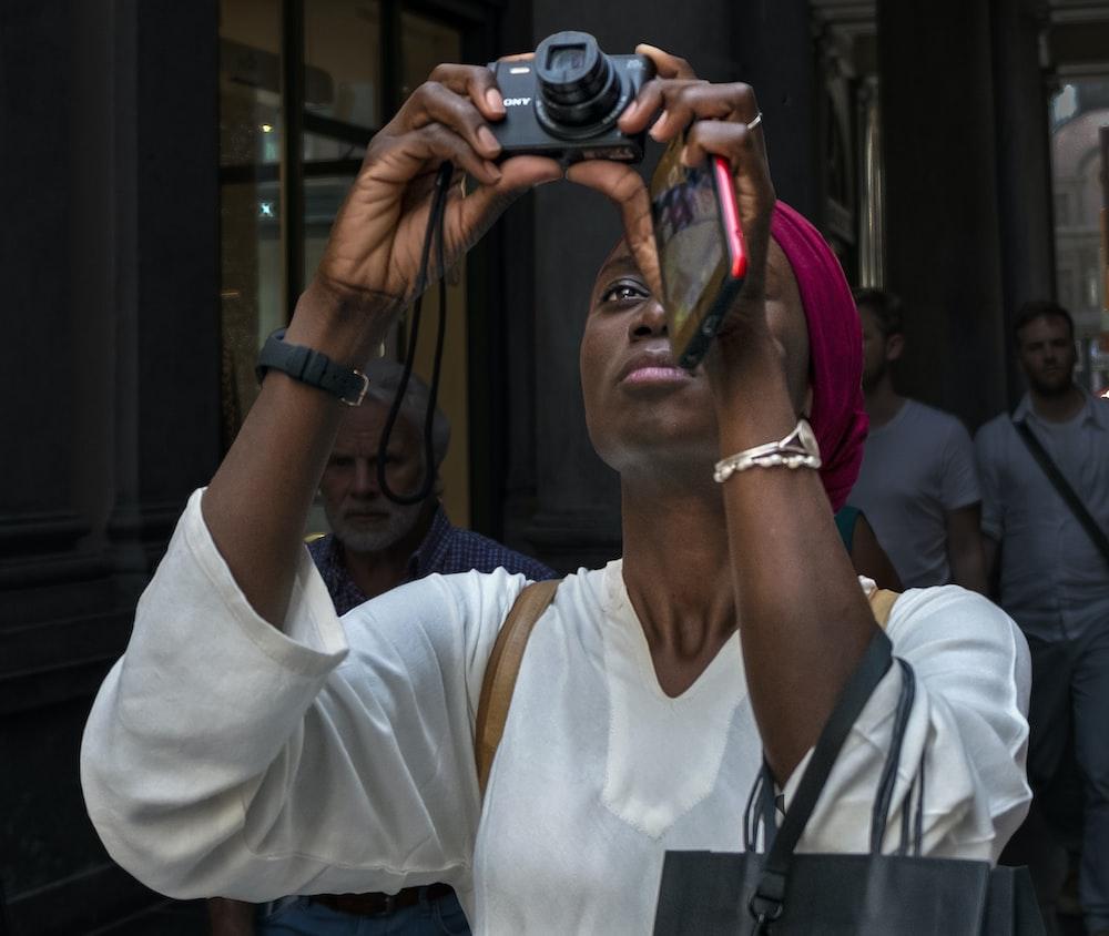 woman looking at point-and-shoot camera