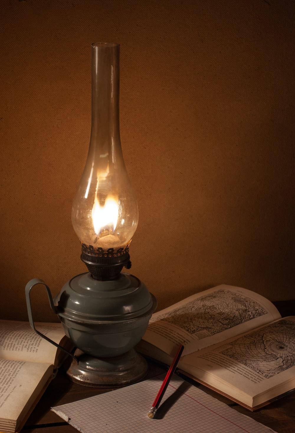 gray oil lamp beside book