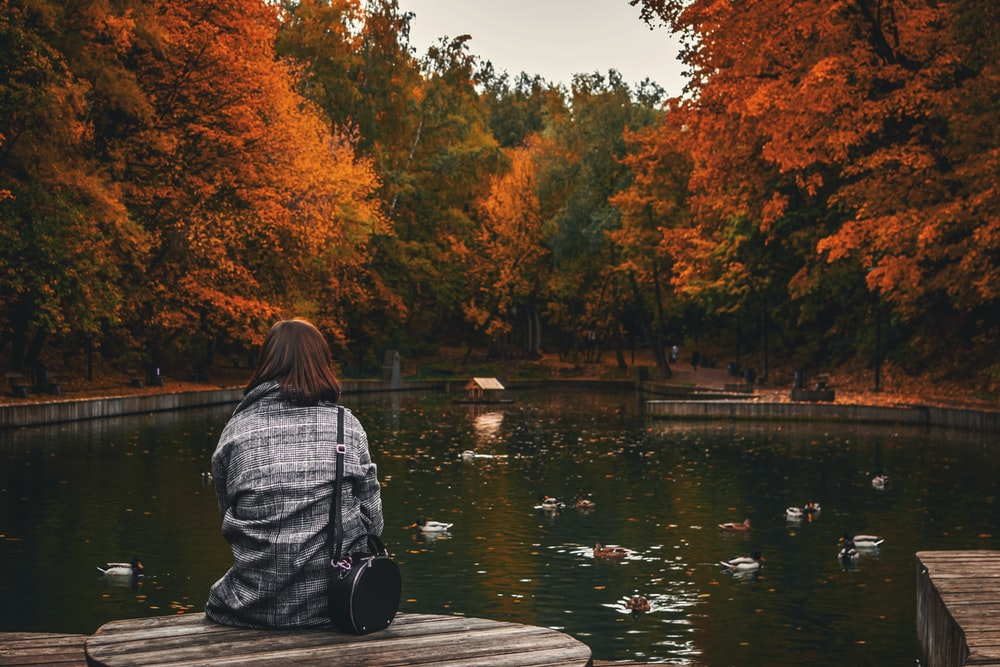 woman sitting on dock during day