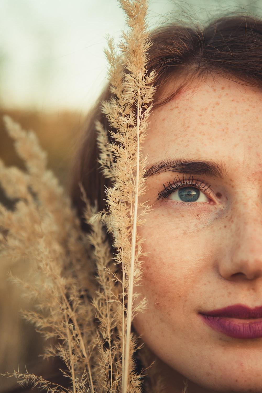 brown grass beside woman's face