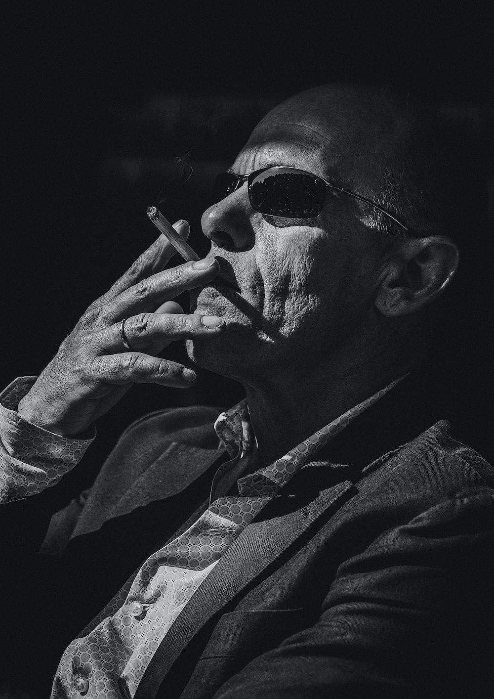 man smokes cigarette in monochrome photo