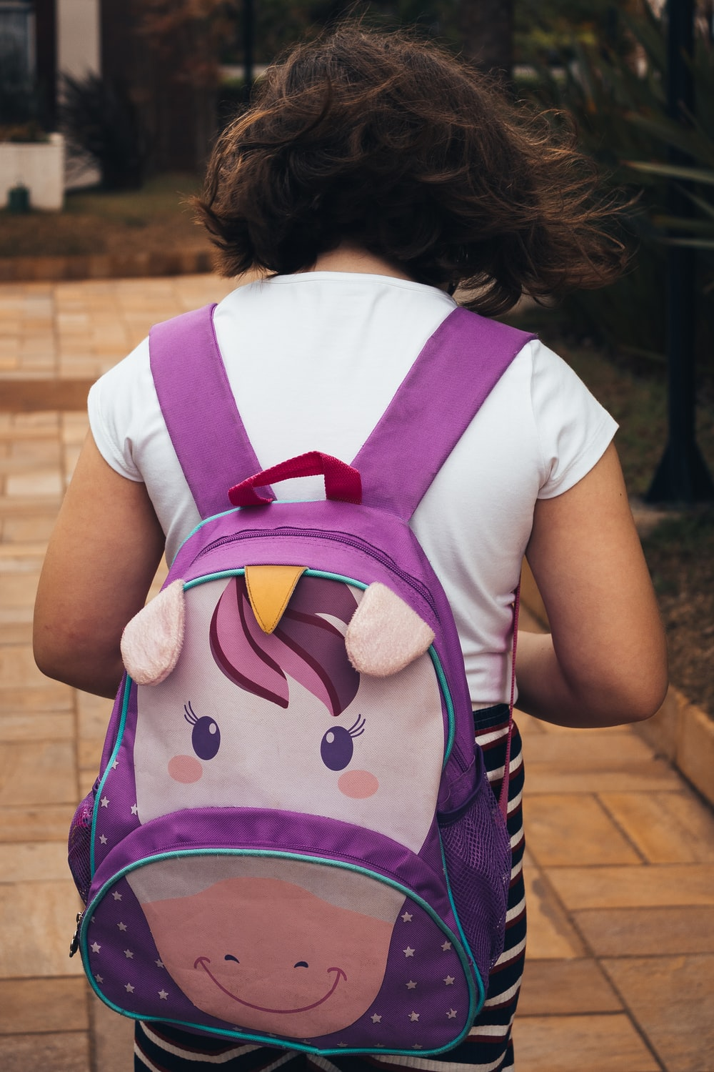 girl in white shirt carrying purple backpack