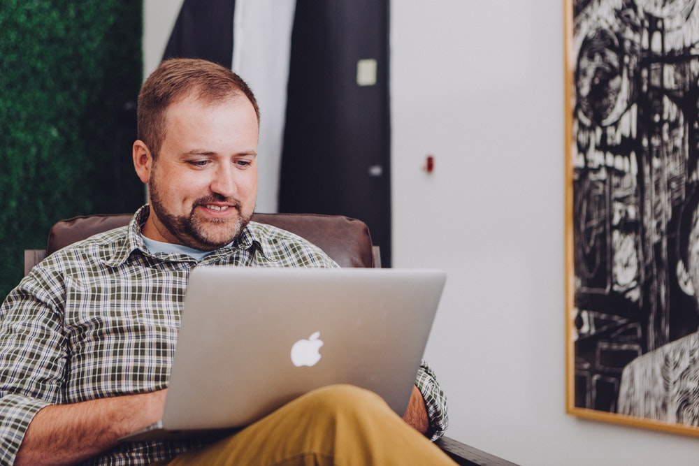 man smiling and using MacBook