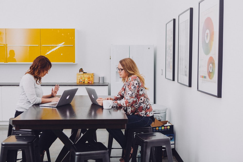 2 women using laptop by table