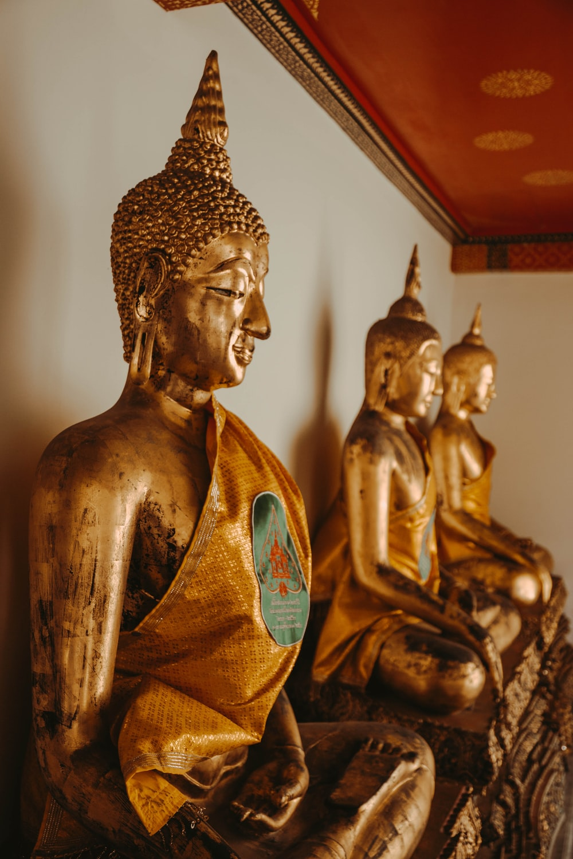 three gold buddha figurines