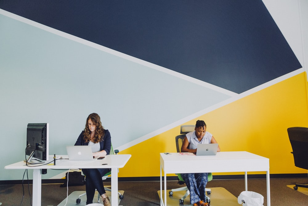 two women sitting beside table using MacBooks