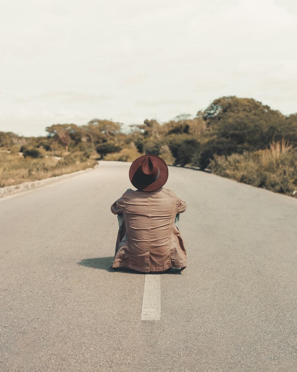 man sitting on empty road