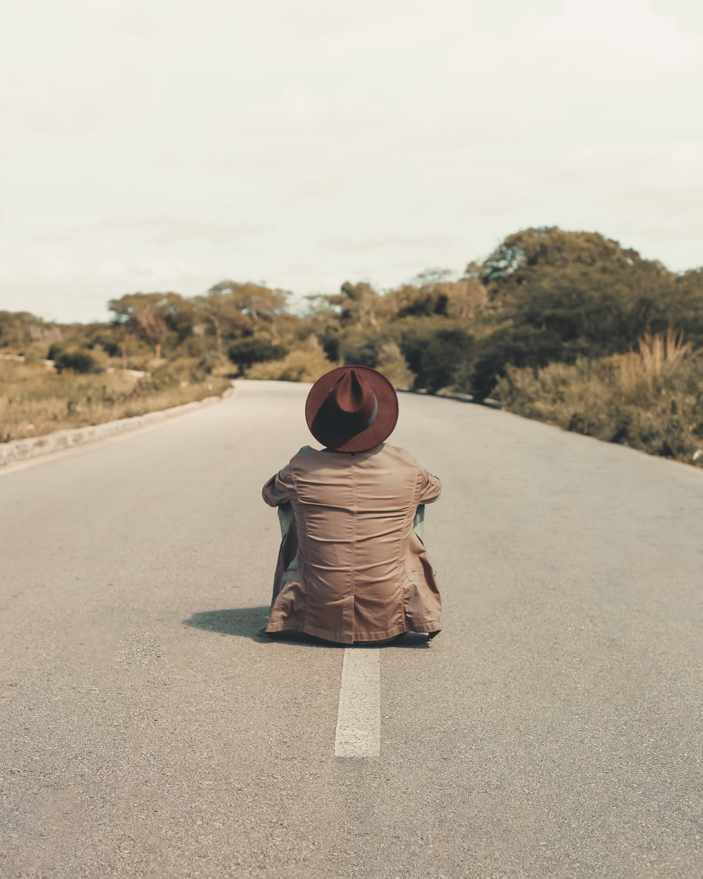 man sitting on empty road