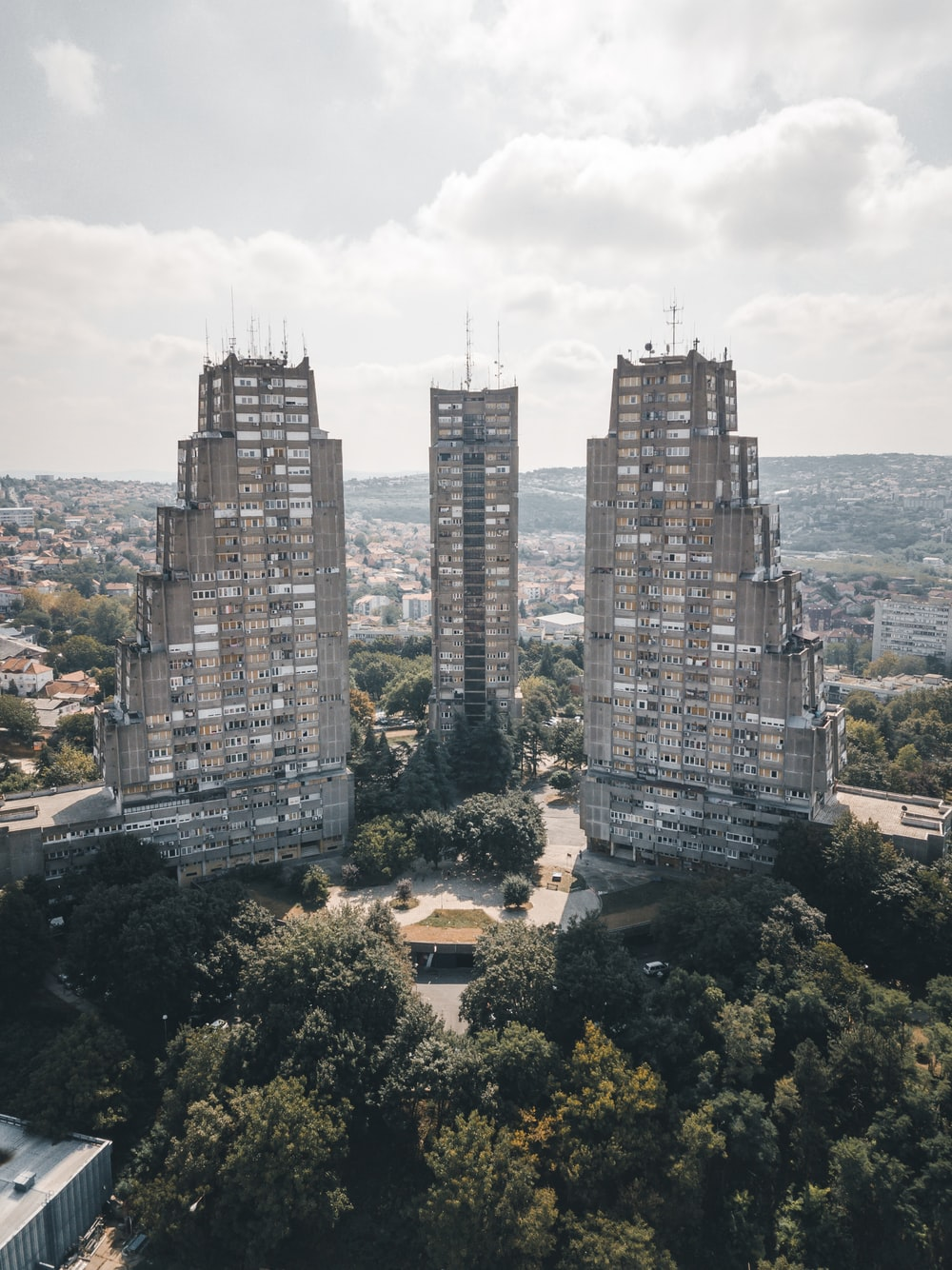 high-rise buildings and trees under cloudy sky