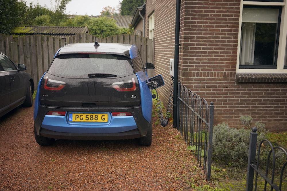 blue hatchback beside house