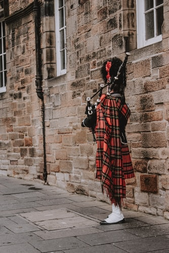 person playing bag pipe on sidewalk