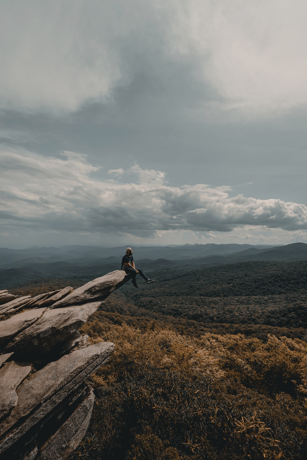 person sitting on brown cliff