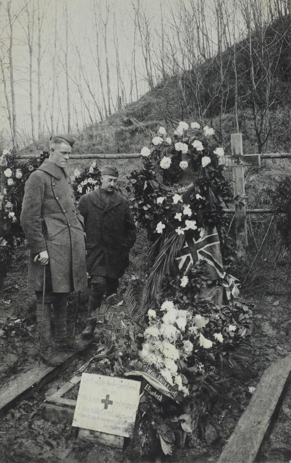 man standing beside grave