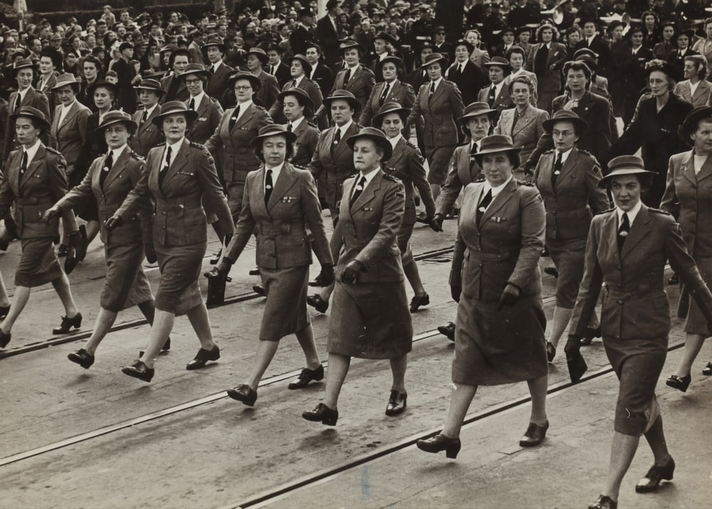 grayscale photography of group of women marching on road