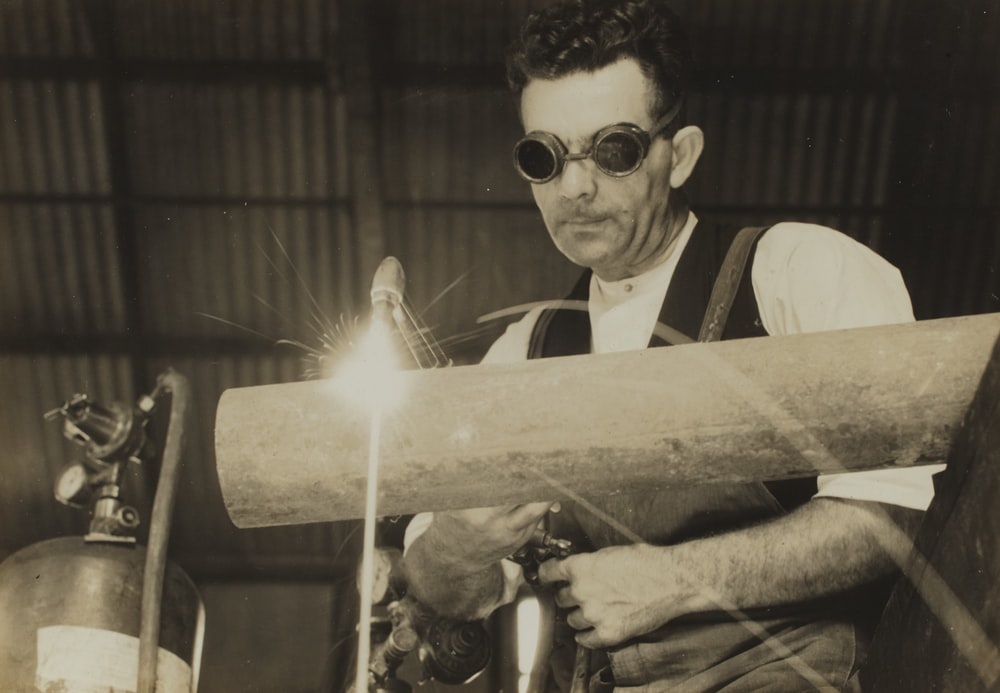 grayscale photography of man welding tube