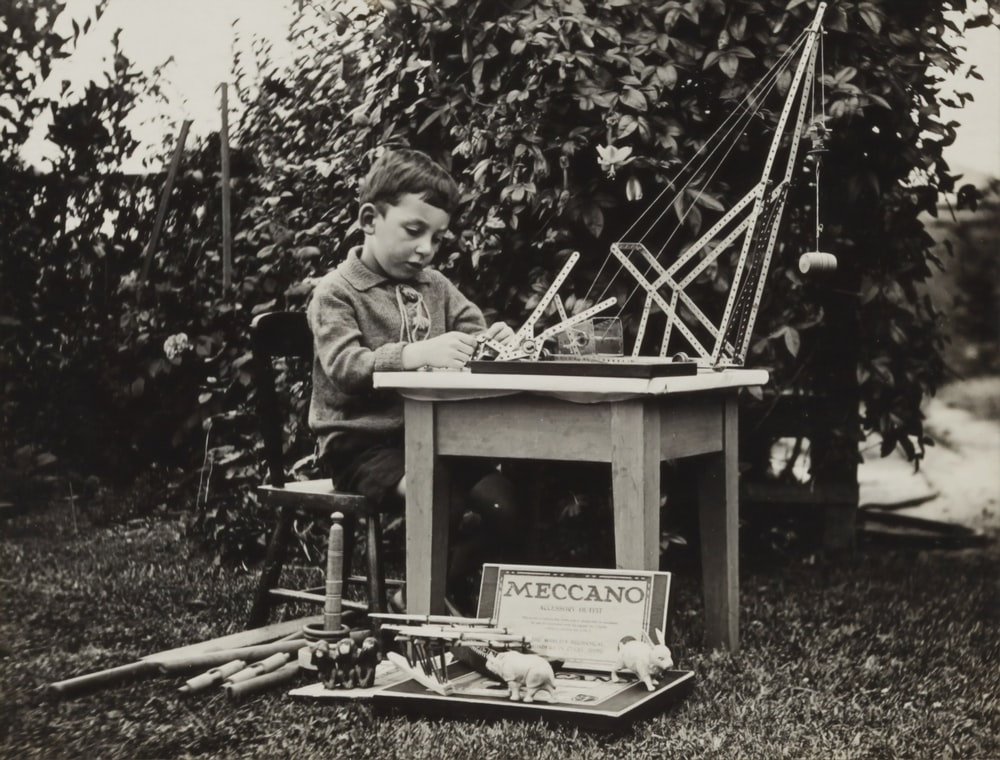 boy sitting on chair playing with meccano