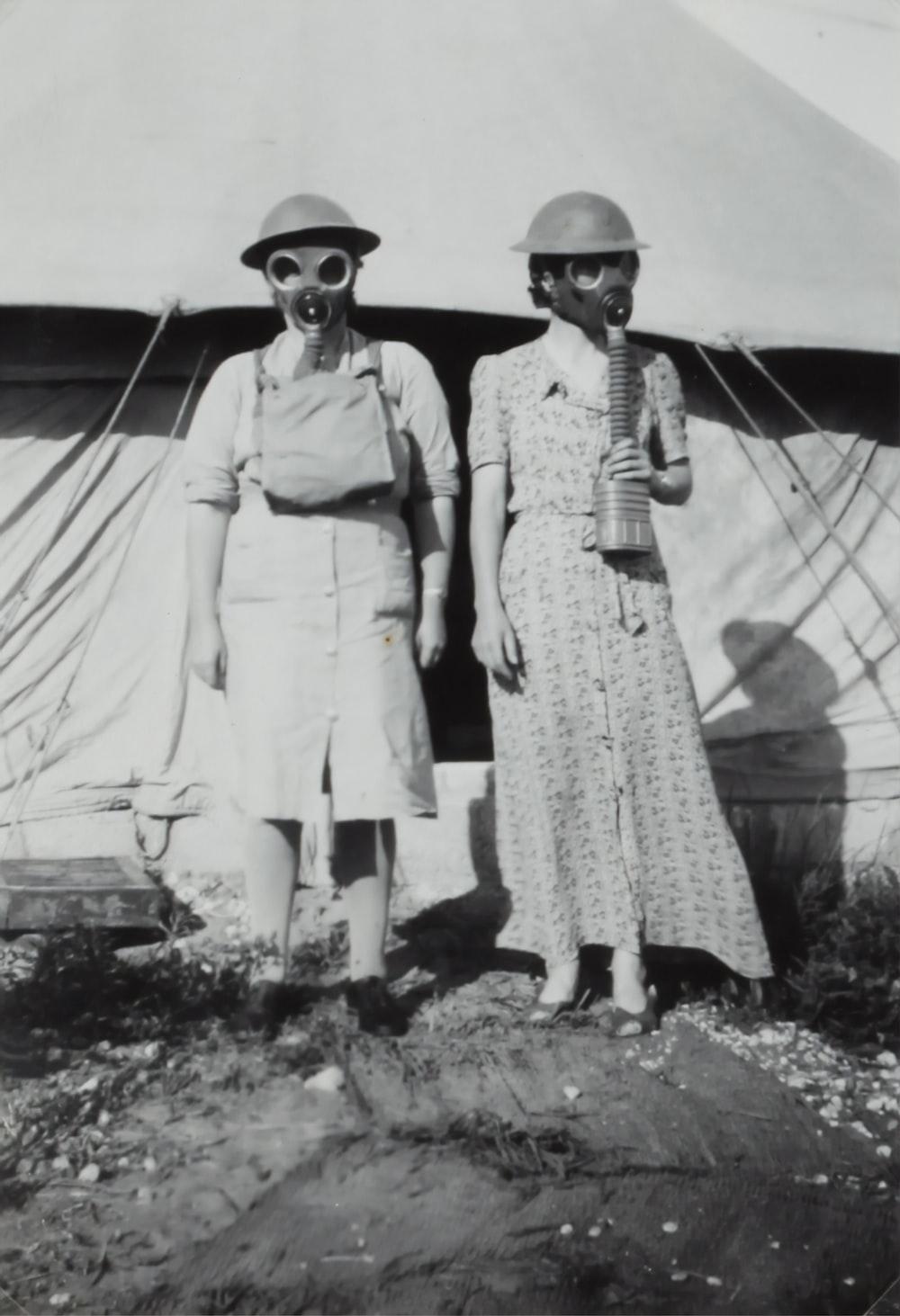 two women wearing gas mask standing beside tent