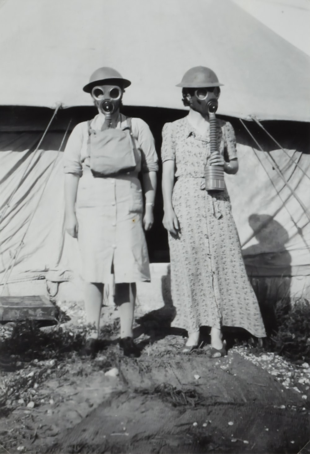 two women wearing gas mask standing beside tent