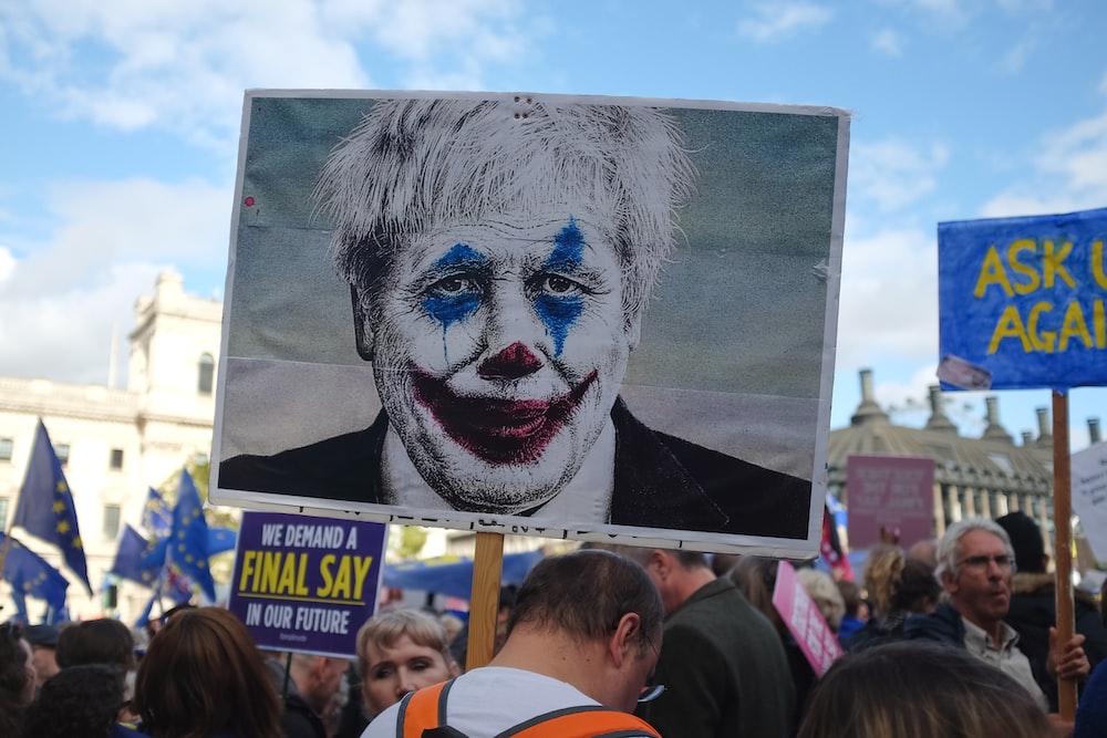 person holding man wearing clown face art