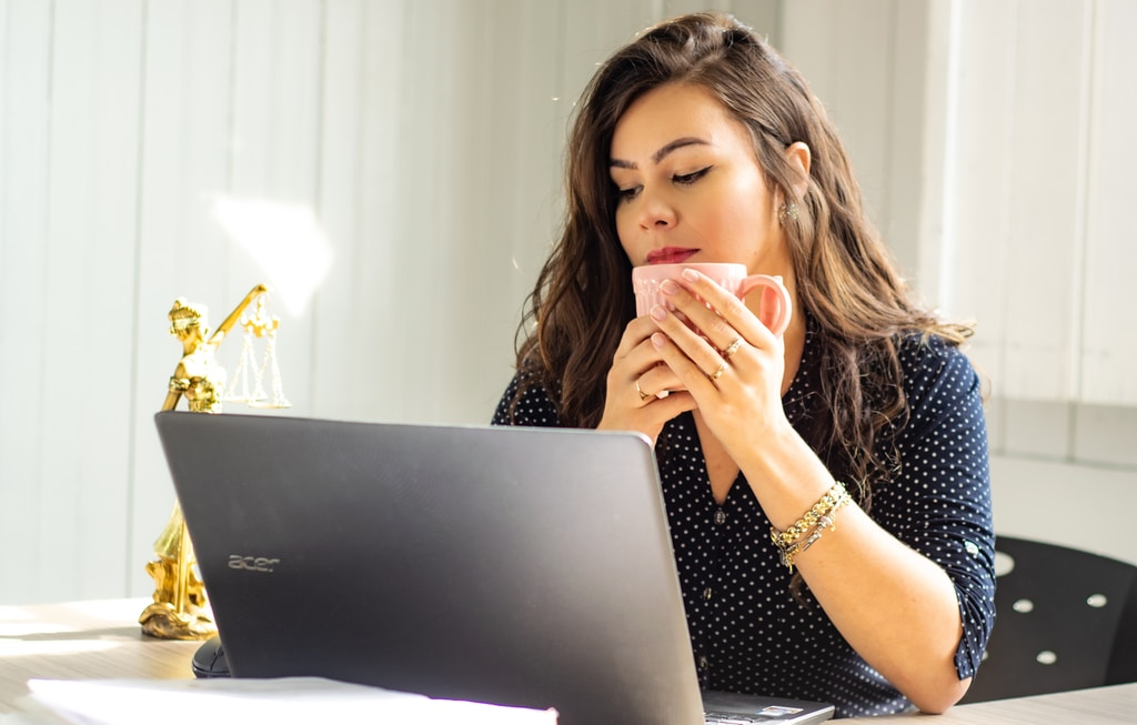 Young woman sitting at desk looking at laptop holding coffee cup