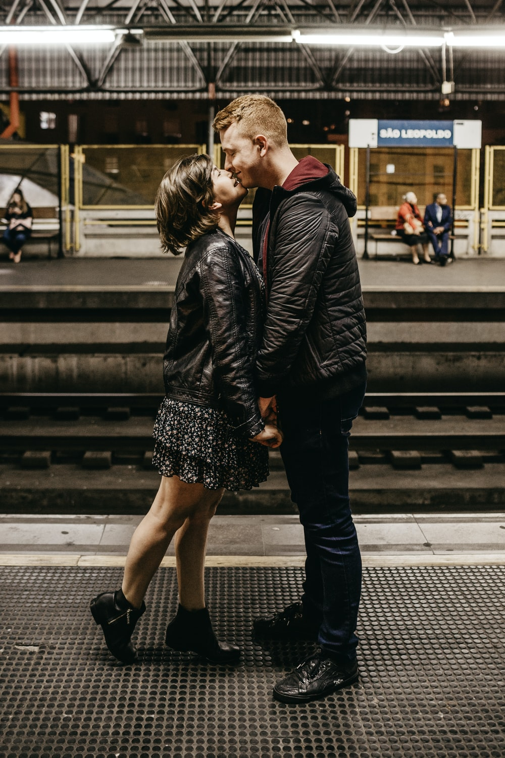 man and woman kissing beside train rails
